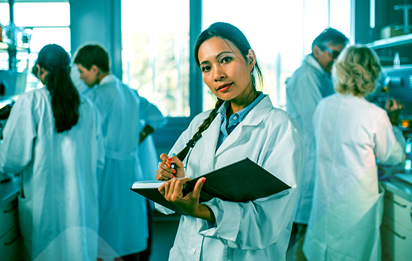 A researcher holding an open notebook and a pen looks up from her notes and out of the screen. The lab is busy with four other researchers behind her.